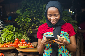 young african woman selling in a local market smiling while using her mobile phone