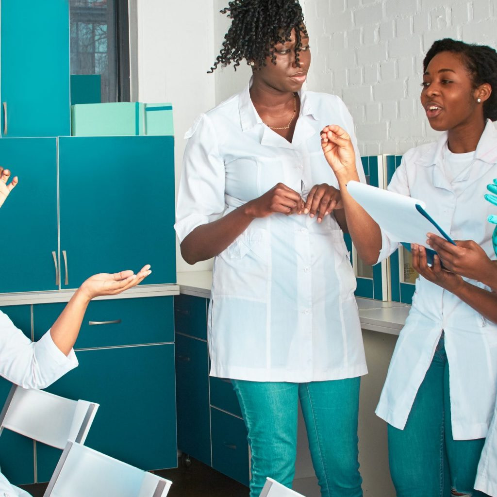 Female African medical students, young graduates or doctors discuss ongoing project. Energetic expressive group discussion in test lab Testing samples from patients with Covid-19 infections disease.
