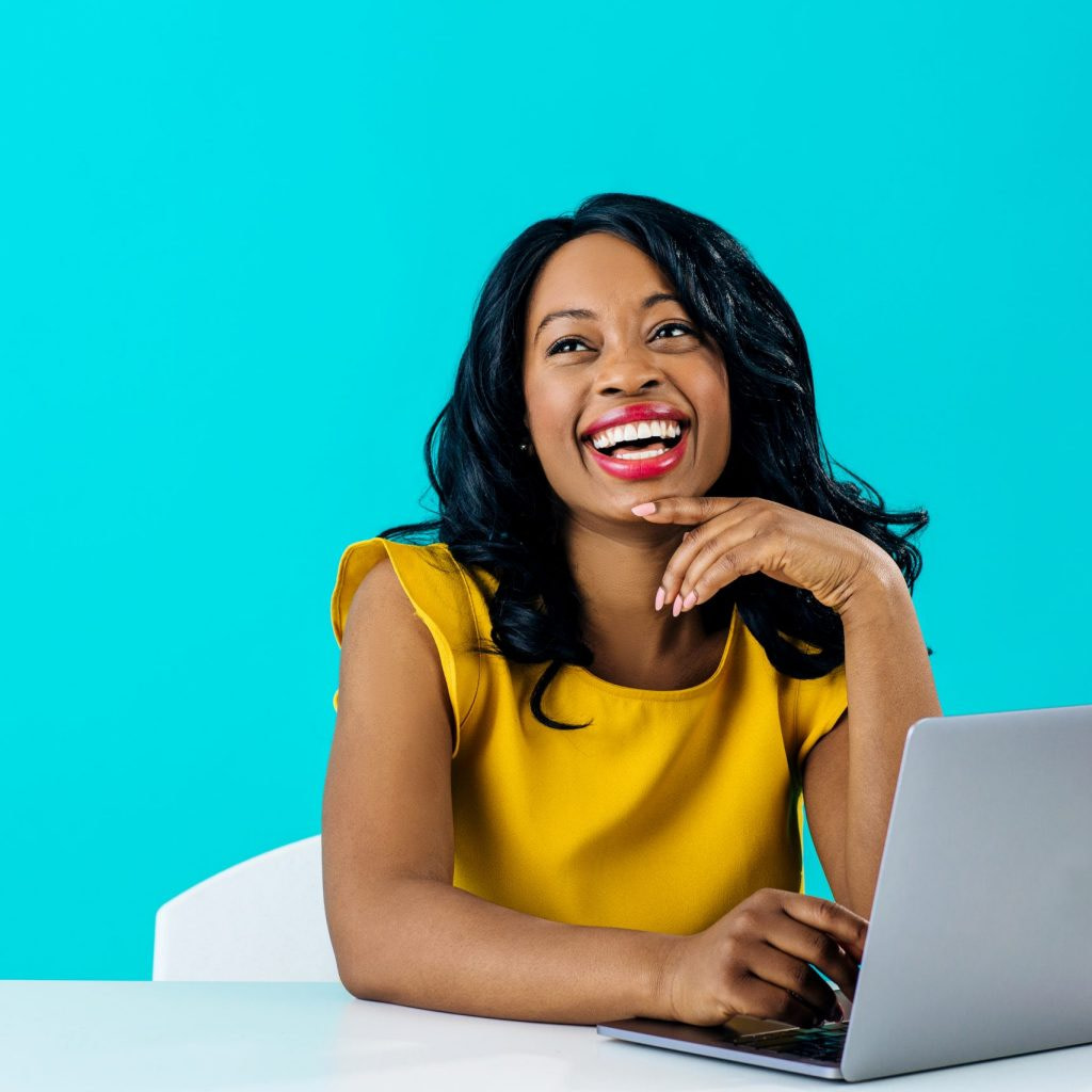 Portrait of a happy young smiling woman sitting behind desk and computer laptop, looking up