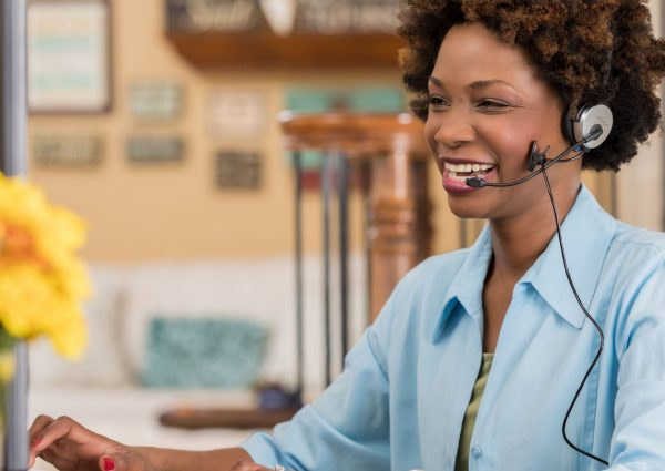 cheerful-african-american-woman-uses-headset-while-talking-with-client-624178502-5ac67795a18d9e00377950cb